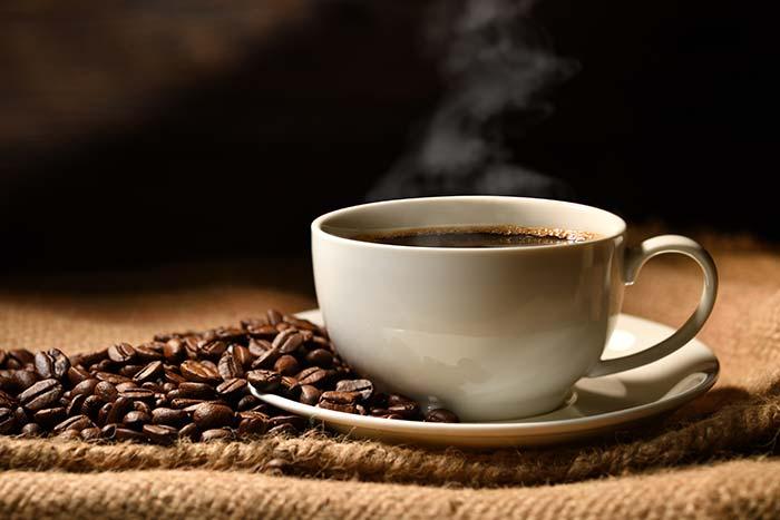 Tasse mit heißem dampfenden Kaffee und Kaffeebohnen daneben